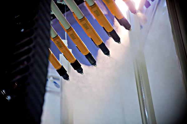 Pistolets de laquage en fonctionnement dans une cabine recouvrant les profilés aluminium dans l'usine de Courmelles de Wicona ©Wicona